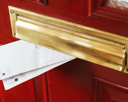mail-peeks-out-from-a-brass-letterbox